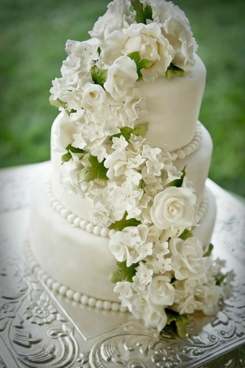 Torte mit Zuckerperlen und weißen Blumen aus Fondant