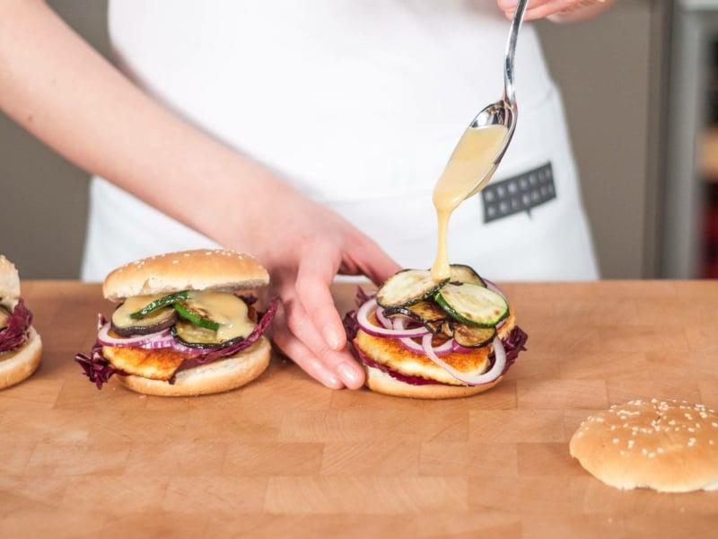 Burger mit Sauce beträufeln