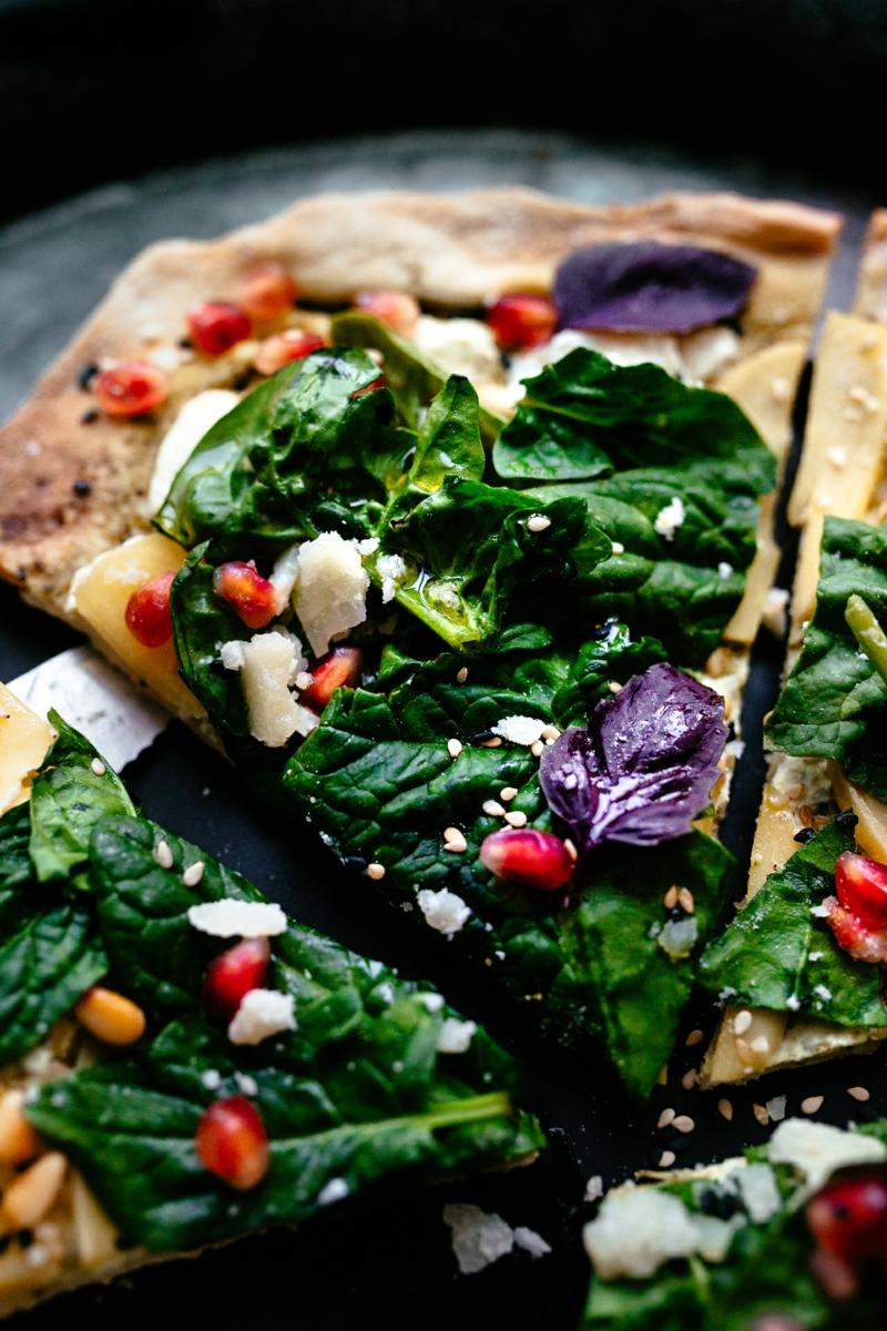 Pizza mit frischem Spinat und Granatapfelkernen