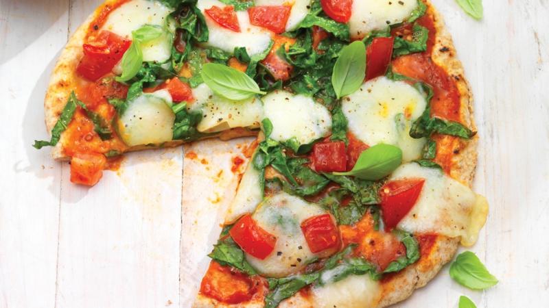 Blattspinat Pizza mit Tomaten und Mozzarella