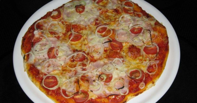 Pizza mit Tomaten und Zwiebelringen