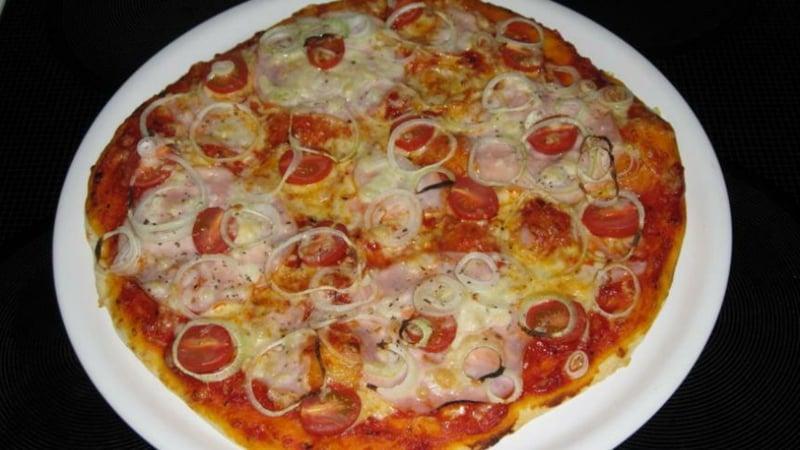 Pizza mit Schinken und Zwiebelringen