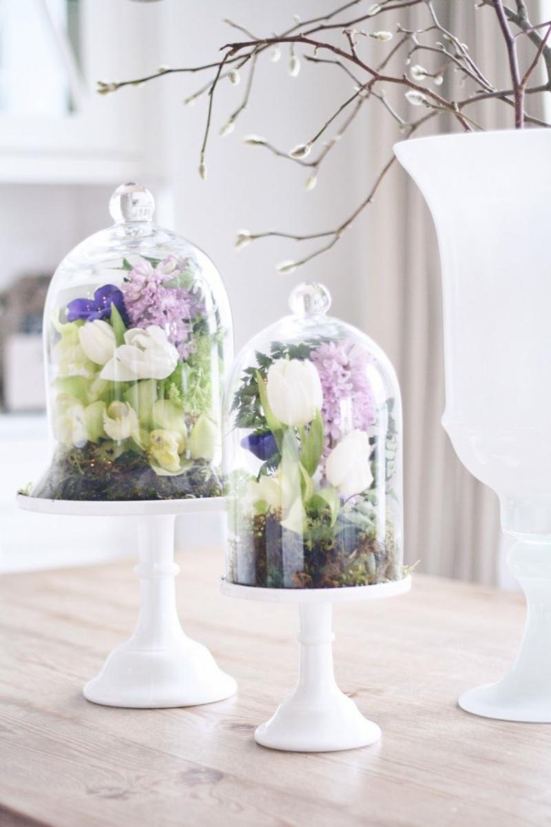 Blumengestecke unter Glasglocken