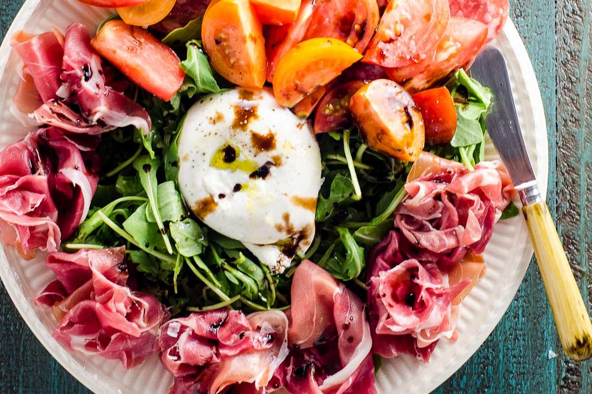 Buratta Rezepte runde Platte mit Proscuitto und Gemüse